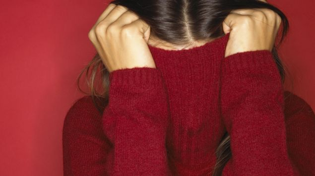 Das Bild zeigt eine Frau, die einen roten Pulli über den Kopf zieht.
