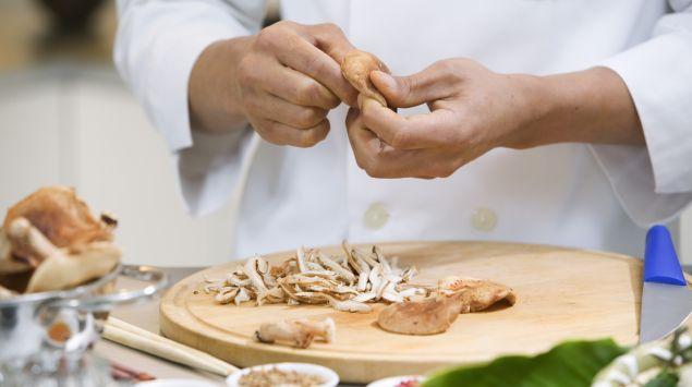 Das Bild zeigt einen Koch beim Zubereiten von Pilzen.