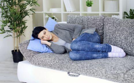 Eine nachdenklich aussehende Frau liegt mit angezogenen Beinen auf einem Sofa.