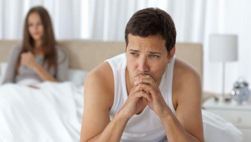 Das Bild zeigt ein Paar im Bett, der Mann sitzt am Bettrand.