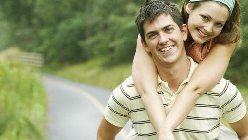 Das Bild zeigt einen Mann, der seine Freundin auf dem Rücken trägt.