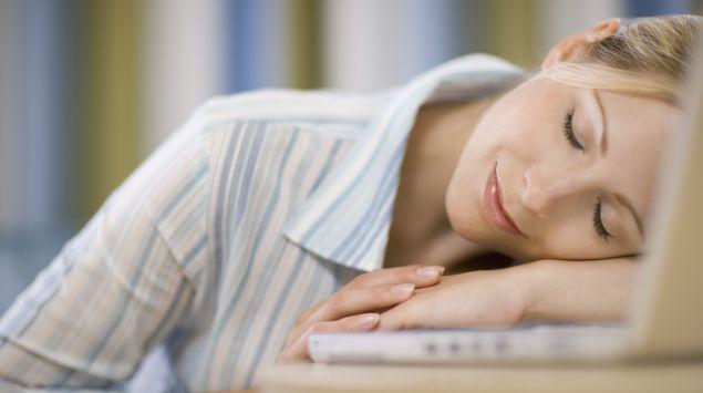 Eine Frau hat den Kopf auf den Schreibtisch gelegt und schläft.