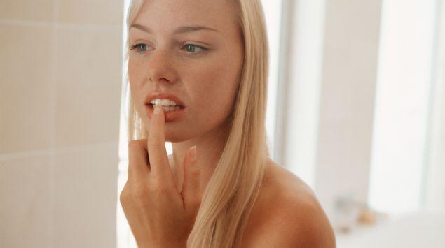 Das Bild zeigt eine Frau, die sich ihre Zähne anschaut.