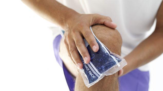 Das Bild zeigt einen Mann, der sein Knie kühlt.