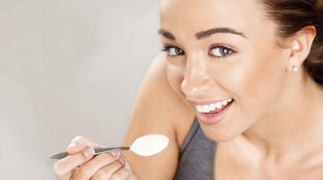 Das Bild zeigt eine junge Frau, die einen Löffel Joghurt isst.