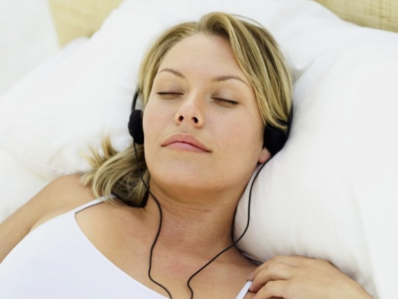 Gastritis: Das Bild zeigt eine Frau mit Kopfhörern und geschlossenen Augen.