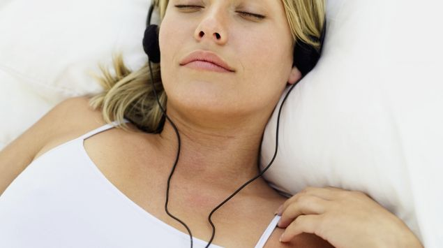 Das Bild zeigt eine Frau mit Kopfhörern und geschlossenen Augen.