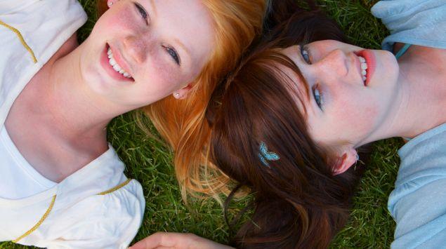 Zwei weibliche Teenager liegen im Gras.