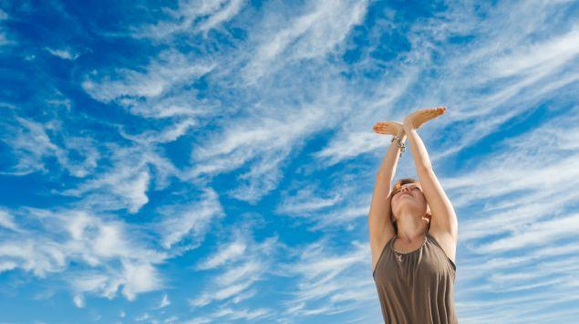 Eine Frau reckt die Hände zum Himmel.