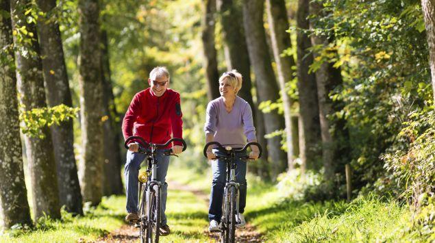 Das Bild zeigt ein Paar mittleren Alters beim Radfahren.
