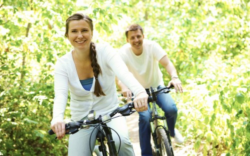Das Bild zeigt ein Paar im Wald beim Radfahren.