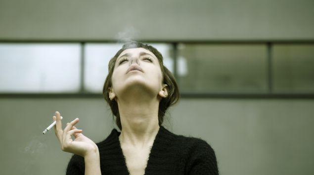 Das Bild zeigt eine Frau beim rauchen.