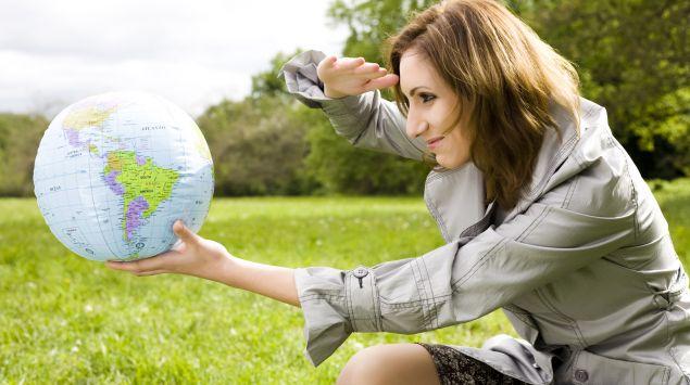 Man sieht eine Frau, die eine Plastikweltkugel in der Hand hält.