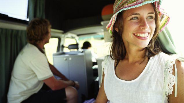 Man sieht eine lachende Frau mit Sonnenhut in einem Campingbus.