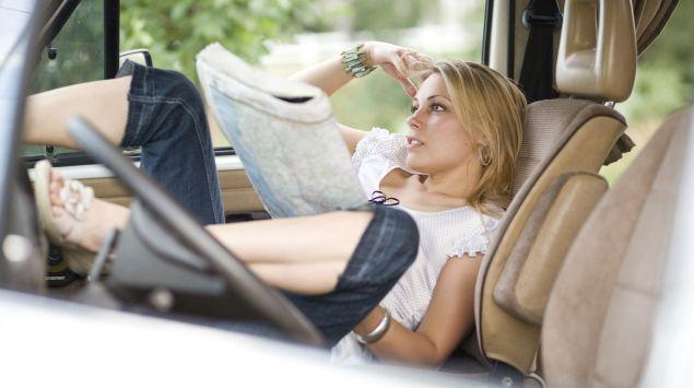 Man sieht eine Frau im Auto, die eine Karte in der Hand hält.