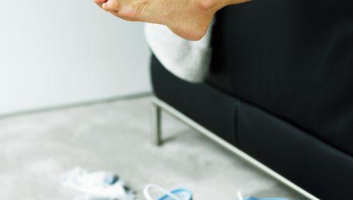 Das Bild zeigt nackte Füße und Sportschuhe.