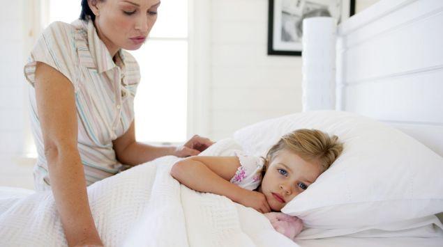Das Bild zeigt ein Kind im Bett und eine Frau am Bettrand sitzend.