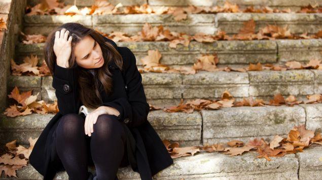 Eine nachdenklich aussehende Frau sitzt auf einer mit herbstlichen Blättern bedeckte Treppe.