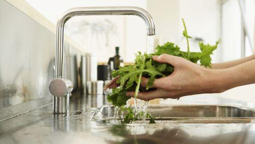 Jemand wäscht Salat.