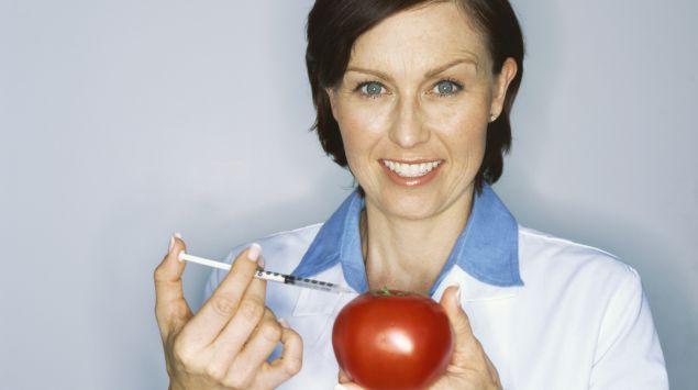 Das Bild zeigt eine Frau, die in eine Tomate spritzt.