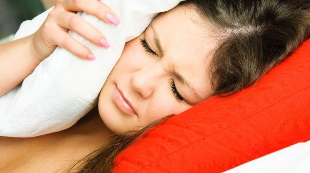 Das Bild zeigt eine Frau, die sich ein Kissen aufs Ohr drückt.