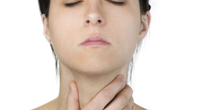 Man sieht eine Frau mit geschlossenen Augen, die sich an den Hals greift.