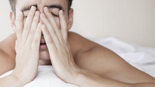 Das Bild zeigt einen Mann, der im Bett liegt und sich die Hände vors Gesicht hält.