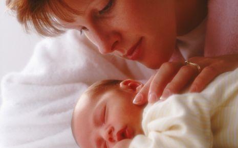 Man sieht eine Frau, die ihr schlafendes Baby betrachtet.