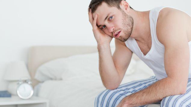 Man sieht einen Mann, der auf einem Bett sitzt und seinen Kopf in der Hand abstützt.
