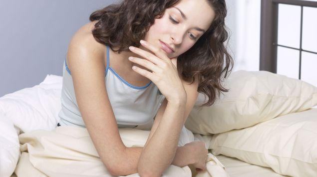 Das Bild zeigt eine Frau im Bett sitzend, auf ihrem Arm aufgestützt.