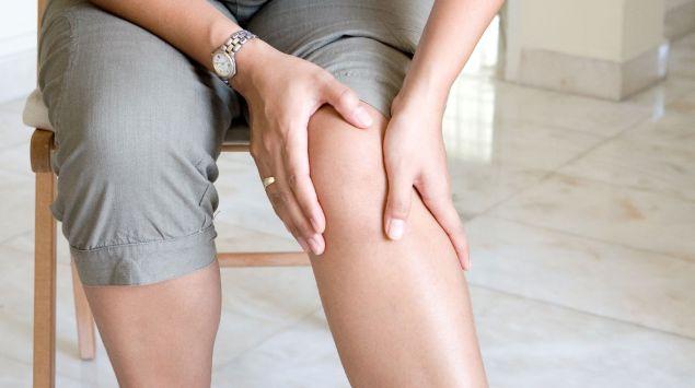 Man sieht eine Frau, die sich ans Knie fasst.