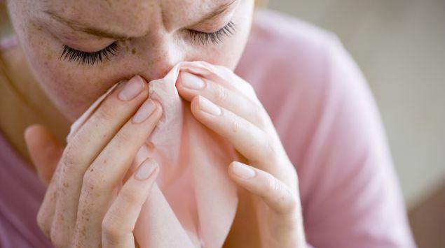 Das Bild zeigt eine Frau, die sich die Nase putzt.