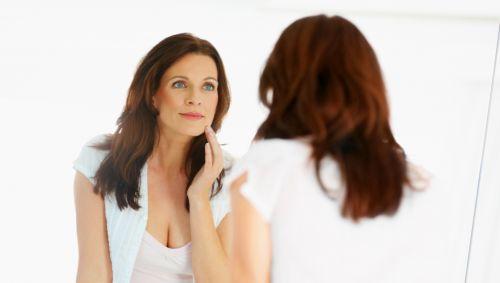 Man sieht eine Frau, die sich im Spiegel betrachtet.