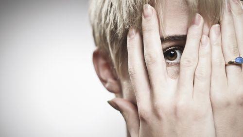 Das Bild zeigt eine Frau, die vorsichtig durch ihre Hände vorm Gesicht lugt.