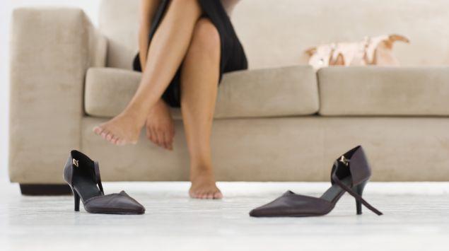 Man sieht eine Frau, die auf dem Sofa sitzt und ihre Schuhe ausgezogen hat.