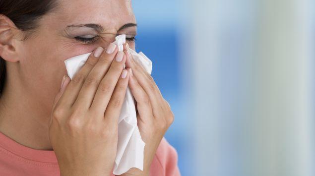 Das Bild zeigt eine Frau beim Naseputzen.