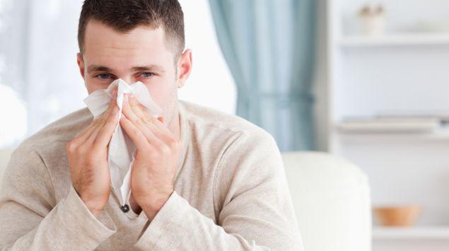 Das Bild zeigt einen Mann beim Naseputzen.