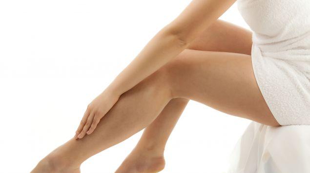 Das Bild zeigt eine Frau, die mit einem Handtuch bekleidet ist sitzend. Der Fokus liegt auf ihren nackten Beine, über die sie mit der Hand fährt.