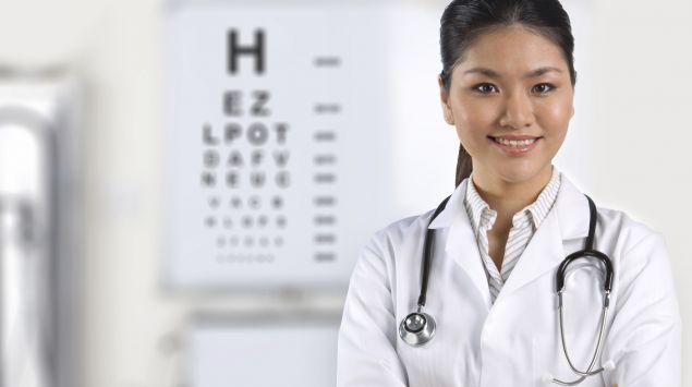 Das Bild zeigt eine Ärztin vor einem Sehtestbild.
