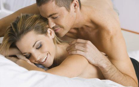 Das Bild zeigt ein nacktes Pärchen auf dem Bett.