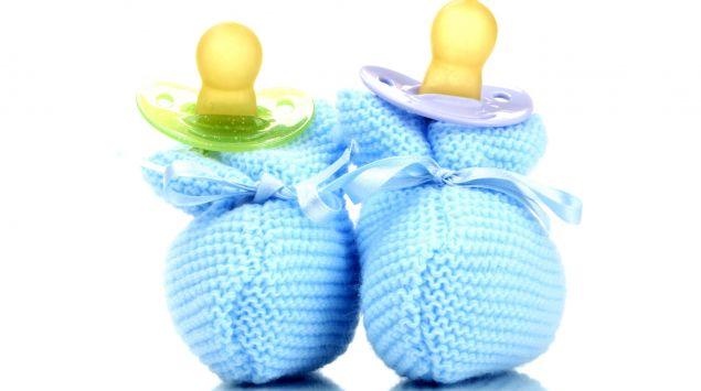 Das Bild zeigt ein Paar blaue Babyschuhe und zwei Schnuller.