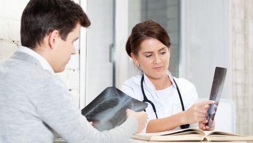 Das Bild zeigt eine Ärztin mit einem Röntgenbild des Patienten.