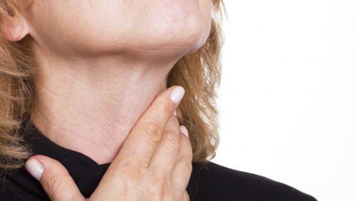 Man sieht eine Frau, die sich an den Hals fasst.