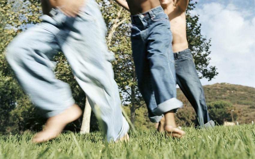 Kinder toben im Sommer auf einer Wiesen.