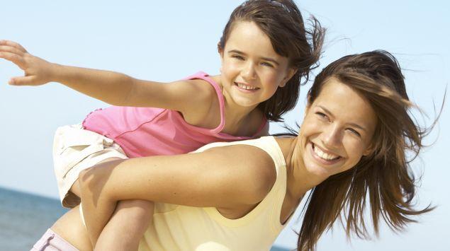 Man sieht eine Frau mit ihrer Tochter auf dem Rücken an einem Strand.