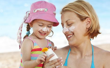 UV-Strahlung: Ein Mädchen mit seiner Mutter am Strand, es trägt einen Sonnenhut, beide haben Creme im Gesicht.