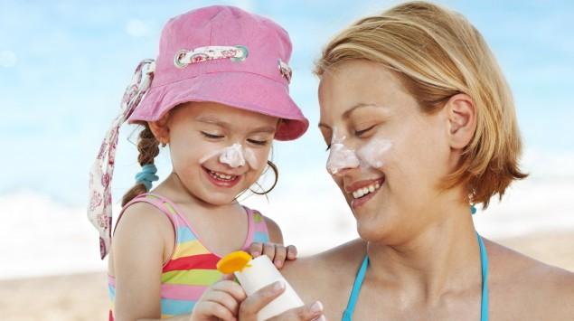Ein Mädchen mit seiner Mutter am Strand, es trägt einen Sonnenhut, beide haben Creme im Gesicht.