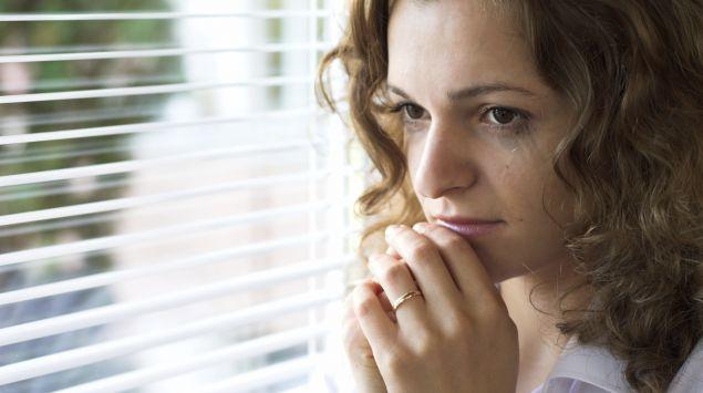 Das Bild zeigt eine Frau, die aus dem Fenster sieht.