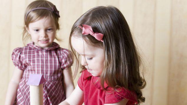 Das Bild zeigt zwei Mädchen, die miteinander spielen.