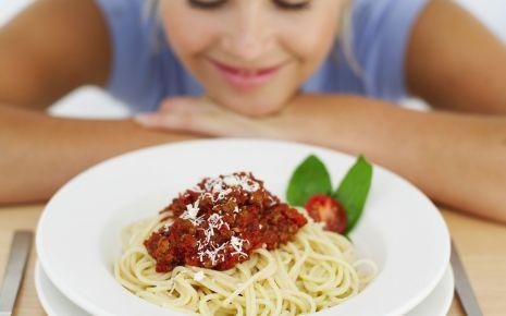 Eine Frau sitzt lächelnd vor einem Teller Spaghetti.